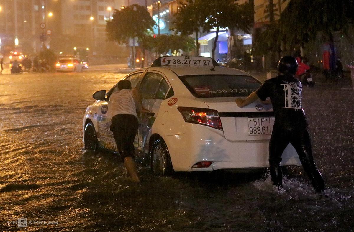 Người dân hỗ trợ tài xế đẩy chiếc taxi chết máy trên đường Nguyễn Hữu Cảnh. Ảnh: Hạ Giang.