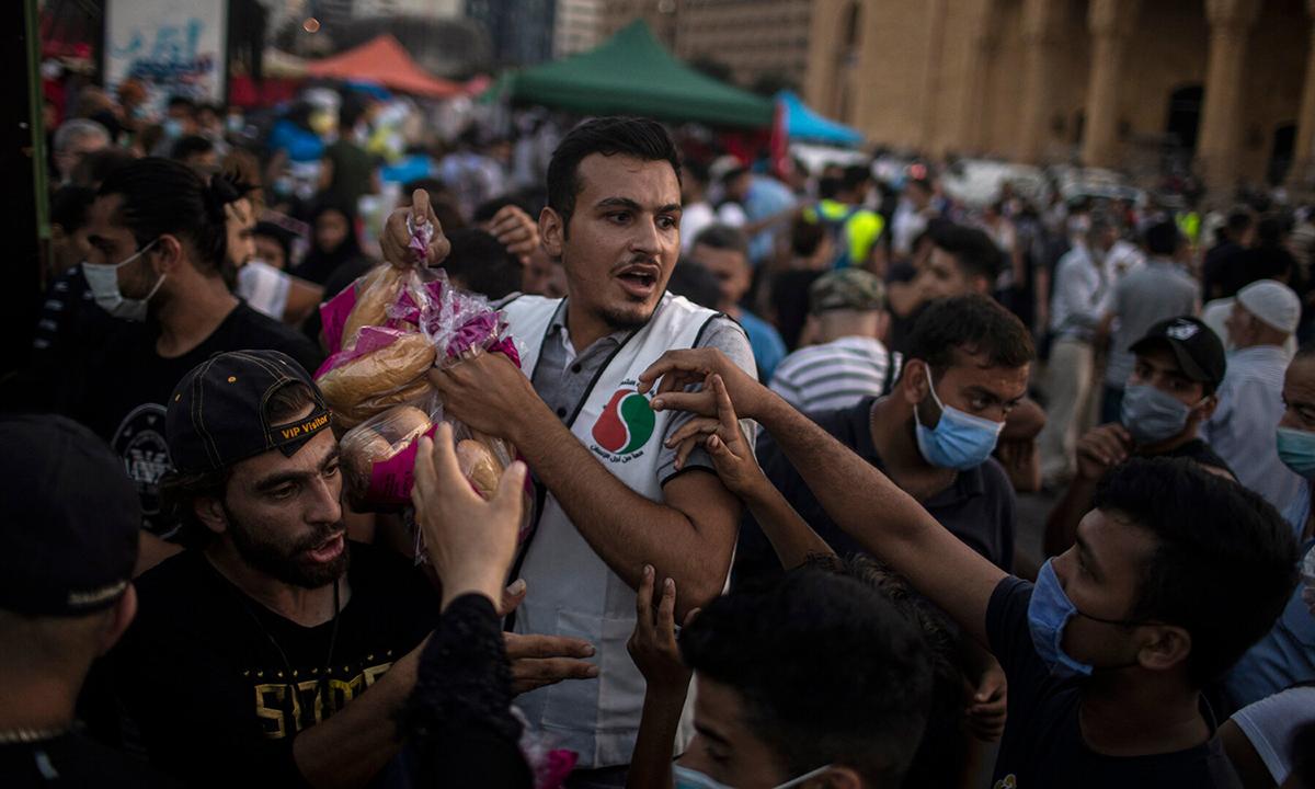 Tình nguyện viên phân phát bánh mì cho người dân sau vụ nổ ở cảng Beirut, hôm 6/8. Ảnh: NYTimes.