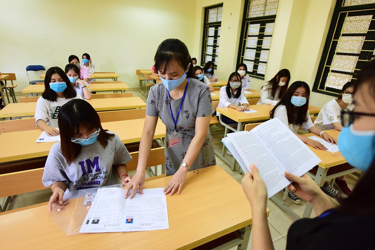 Cán bộ coi thi tại điểm thi trường THPT Phan Huy Chú - Đống Đa (Hà Nội) kiểm tra phiếu dự thi của thí sinh trong chiều 8/8. Ảnh: Giang Huy.