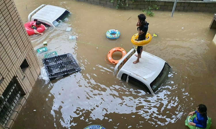 Một người đàn ông bị mắc kẹt vì lũ lụt ở quận Hadong, phía đông nam Hàn Quốc. Ảnh: Yonhap.