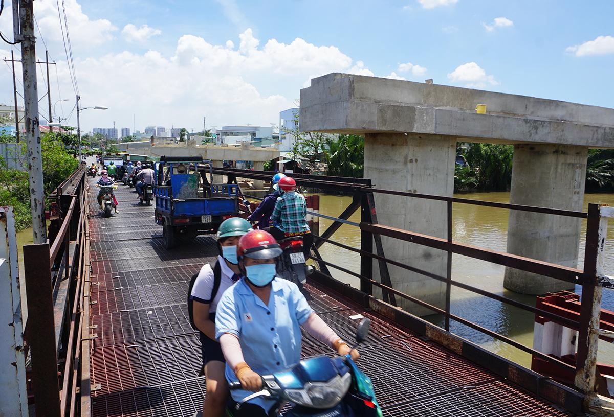 Do dự án cầu Long Kiểng mới chậm tiến độ kéo dài nên hàng ngày người dân Nhà Bè vẫn phải đi qua cầu sắt nhỏ hẹp. Ảnh: Gia Minh.