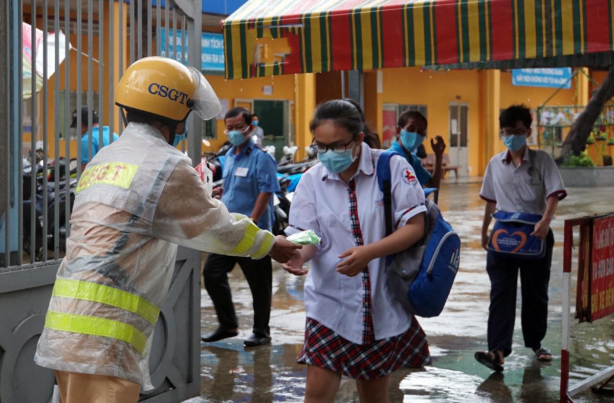 Thượng uý Lê Vũ Thanh Vương, Đội CSGT Bến Thành phát áo mưa cho thí sinh sau giờ thi Toán chiều 9/8 tại điểm thi Ernst Thälmann (quận 1). Ảnh: Mạnh Tùng.