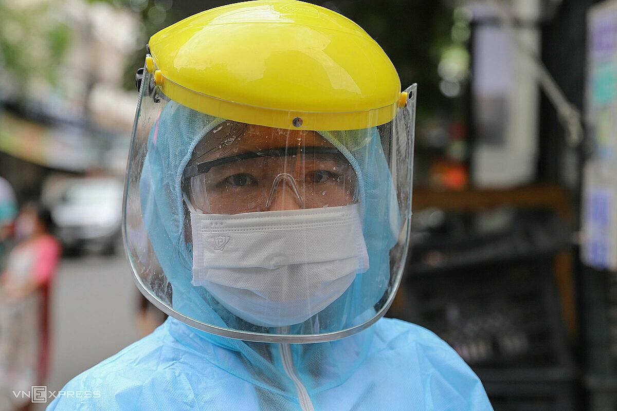 Nữ nhân viên y tế mang đồ bảo hộ kín mít khi lấy mẫu xét nghiệm cho người dân, ngày 3/8. Ảnh: Nguyễn Đông.