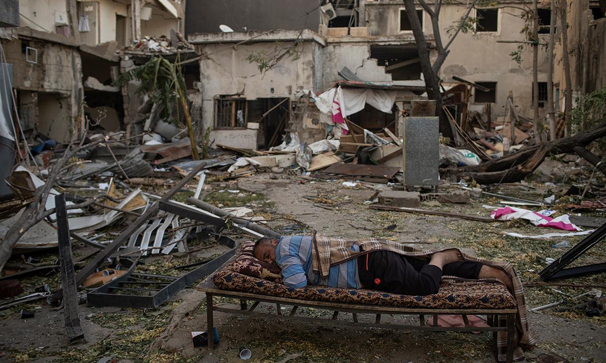 Một người đàn ông nằm ngủ bên ngoài căn nhà bị phá hủy sau vụ nổ ở khu phố Quarantine, thủ đô Beirut, tuần trước. Ảnh: NYTimes.
