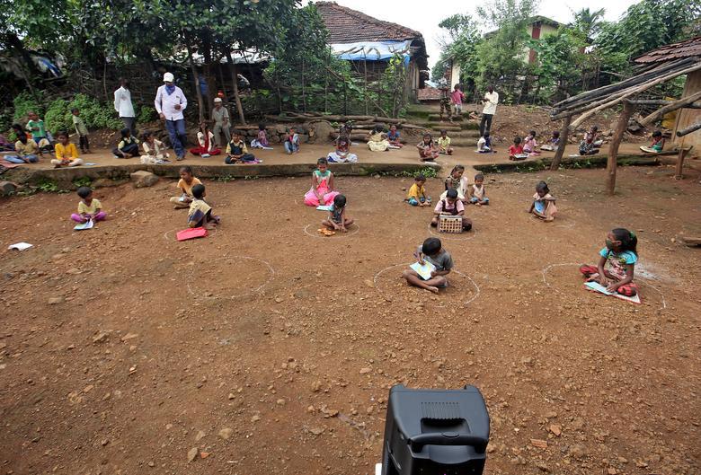 Học sinh ngồi trong vòng tròn, nghe bài giảng phát ra từ chiếc loa kéo di động. Ảnh: Prashant Waydande/ Reuters.