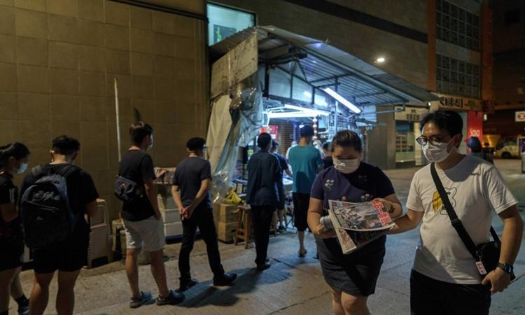 Người Hong Kong xếp hàng tại một sạp báo ở quận Mong Kok để mua ấn phẩm của Apple Daily hôm 11/8. Ảnh: AFP.