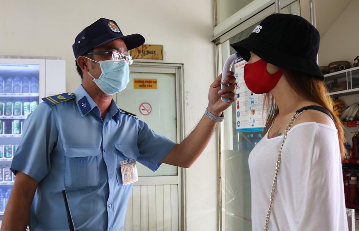 Bảo vệ đo thân nhiệt hành khách tại Bến xe Miền Đông, ngày 10/8. Ảnh: Gia Minh