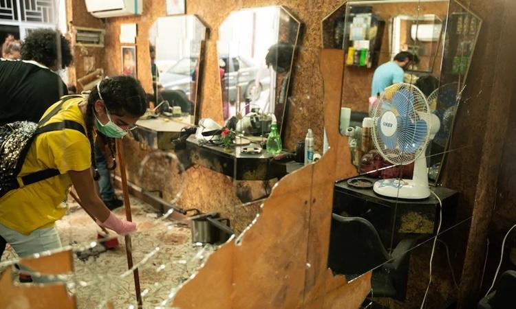 Tình nguyện viên dọn dẹp một tiệm cắt tóc ngày 10/8. Ảnh: Washington Post.