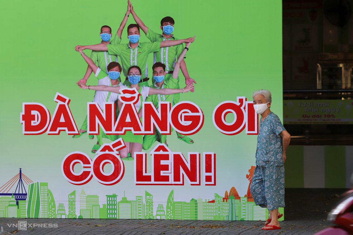 Một người dân đi qua tấm pano cổ động trên đường Lê Duẩn (quận Hải Châu) trong thời gian cách ly xã hội. Ảnh: Nguyễn Đông.
