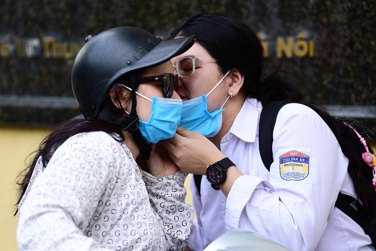 Người mẹ đưa con đi thi tại điểm thi THPT Chu Văn An, Hà Nội, sáng ngày 9/8. Ảnh: Giang Huy.