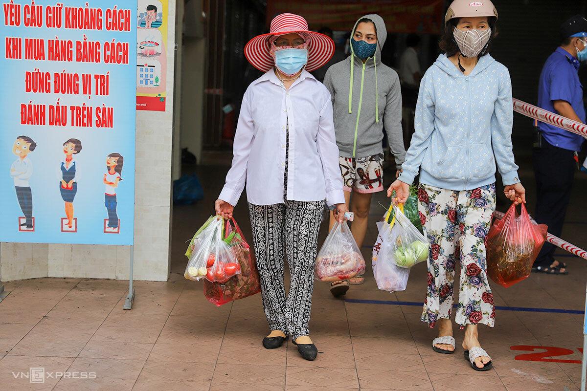 Các bà nội trợ tay xách đầy thịt cá bởi theo quy định ba ngày mới được đi chợ một lần. Ảnh: Nguyễn Đông