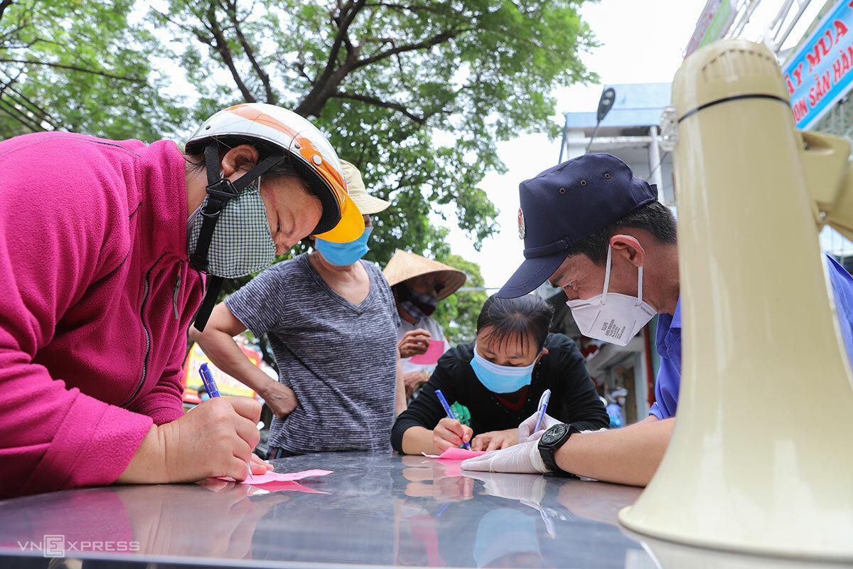 Bảo vệ chợ Cồn ghi thông tin người dân đi chợ, sáng 12/8. Ảnh: Nguyễn Đông