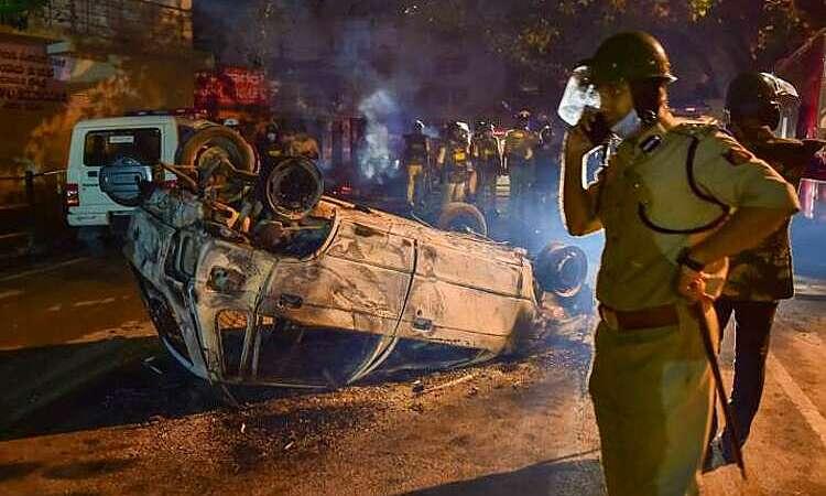 Cảnh sát bên một chiếc xe bị người biểu tình đốt cháy ở Bangalore, Ấn Độ, ngày 12/8. Ảnh: PTI.