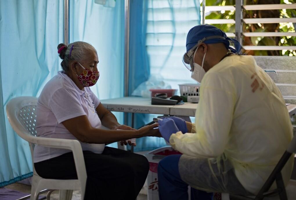 Y tá lấy mẫu máu của người phụ nữ tại El Salvador ngày 30/7. Ảnh: AFP.
