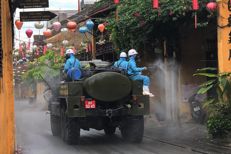 Lực lượng quân sự phun hóa chất khử trùng trên các tuyến dường phố cổ Hội An. Ảnh: Đại Ba.