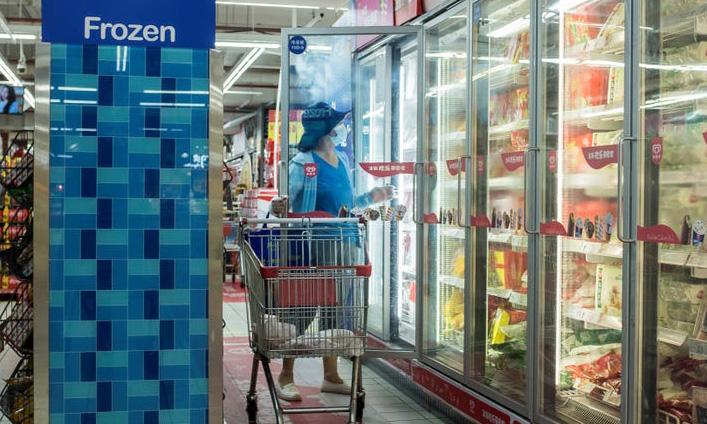 Một phụ nữ chọn thực phẩm đông lạnh tại một siêu thị ở Bắc Kinh, Trung Quốc, hôm 13/8. Ảnh: Reuters.
