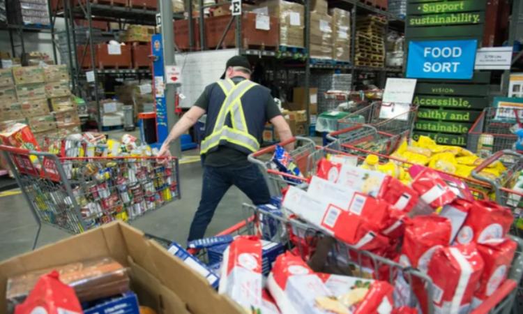 Nhân viên của GVFB vận chuyển hàng hóa tại Burnaby,  British Columbia, Canada, hôm 18/3. Ảnh: The Canadian Press.
