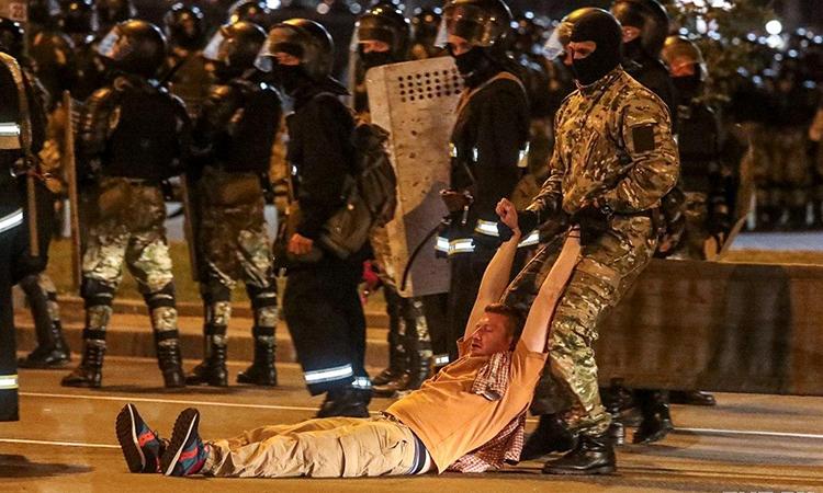 Cảnh sát Belarus lôi một người biểu tình khỏi khu vực đụng độ tại thủ đô Minsk, ngày 9/8. Ảnh: Reuters.