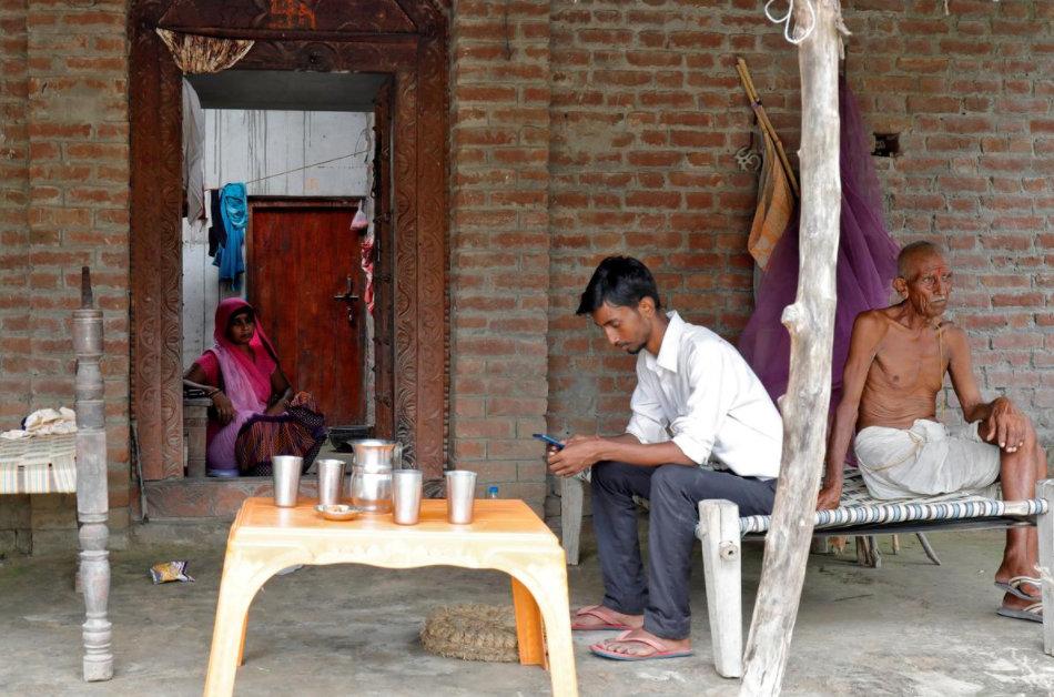 Kumar ngồi xem điện thoại trong nhà cùng bố mẹ hôm 10/8. Ảnh: Reuters.