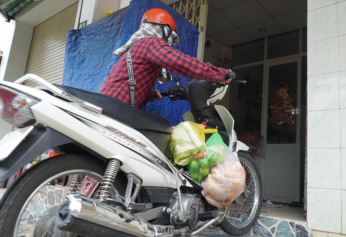 Một người dân mua nhu yếu phẩm về nhà trước giờ cách ly 10 phút. Ảnh: Phước Tuấn