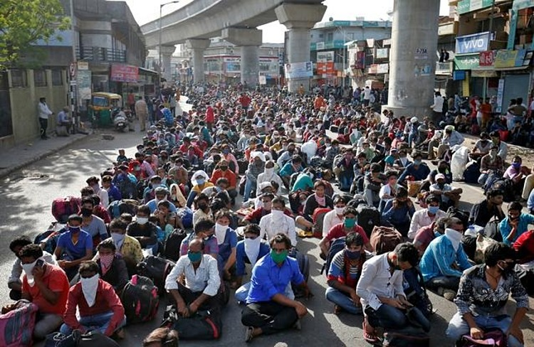 Công nhân di cư và gia đình đợi tàu về quê ở Ahmedabad, hôm 14/5. Ảnh: Reuters