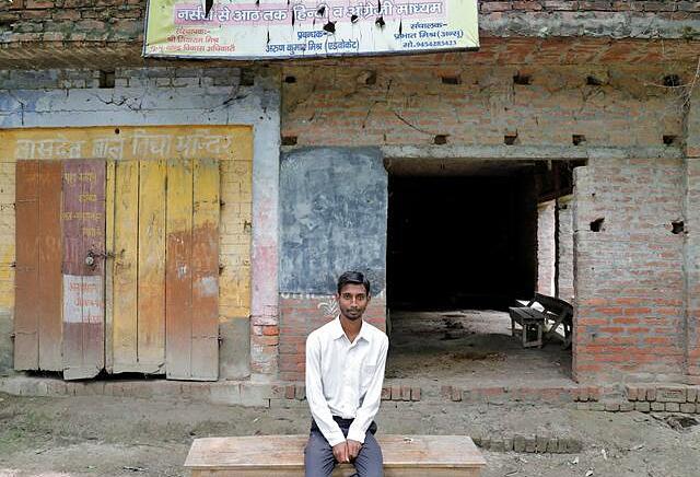 Ashish Kumar, 20 tuổi, ngồi trước ngôi trường tiểu học đổ nát nơi cậu từng theo học ở làng Duttar Nagar, huyện Gonda, bang Uttar Pradesh, hôm 10/8. Ảnh: Reuters