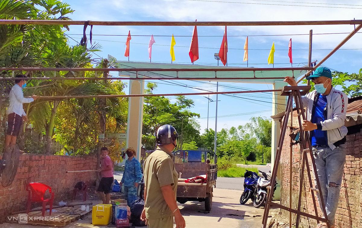 Lực lượng chức năng dỡ bỏ  chốt kiểm soát ở khối 7B, phường Điện Nam Đông sáng 18/8. Ảnh: Đắc Thành.