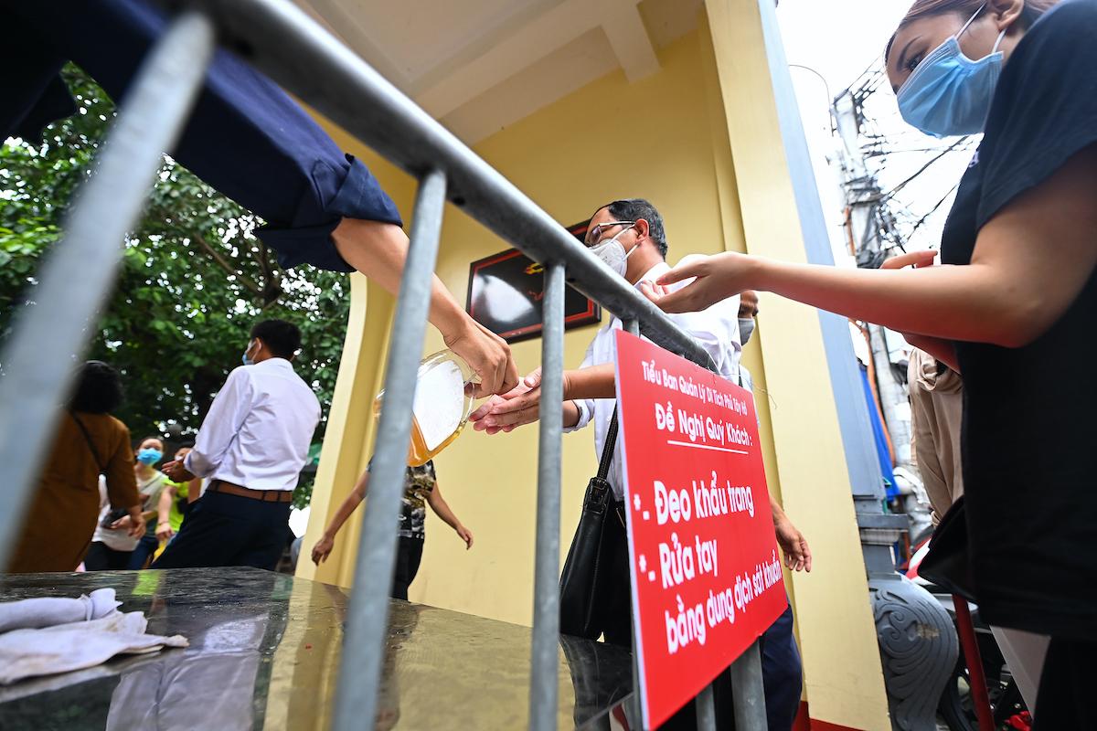 Công an phường Quảng An dựng barie ở cổng ra vào phủ Tây Hồ để yêu cầu người dân xếp hàng giãn cách. Ảnh: Giang Huy