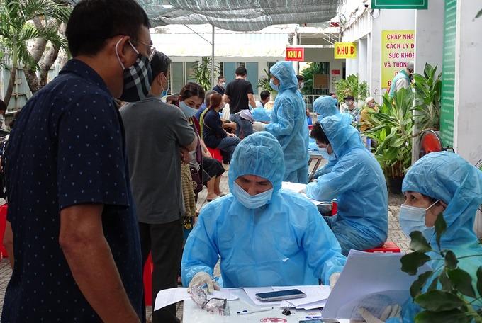 Nhân viên y tế quận Gò Vấp lấy mẫu xét nghiệm người dân từng đến Đà Nẵng, sáng 31/7. Ảnh: Hà An.