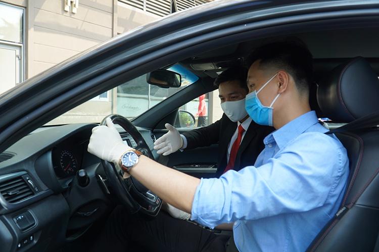Tư vấn viên Kia Việt Nam (mặc vest) hướng dẫn khách lái thử xe.
