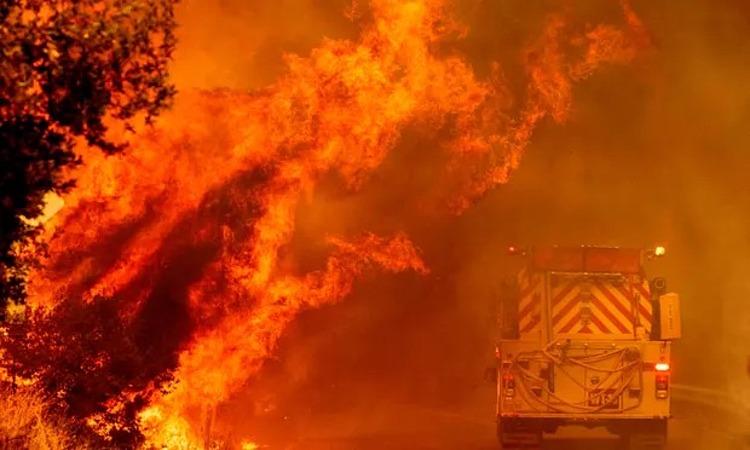 Xe cứu hỏa lao qua lửa khi đám cháy Hennessey tiếp tục bùng phát dữ dội ngoài tầm kiểm soát gần hồ Berryessa ở Napa, California, hôm 19/8. Ảnh: AFP.