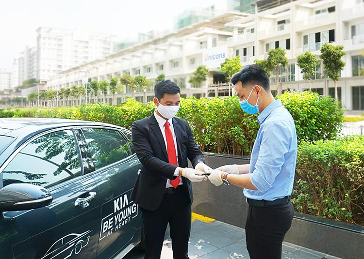 Khách hàng (áo xanh) nhận chìa khoá lái thử xe Kia.