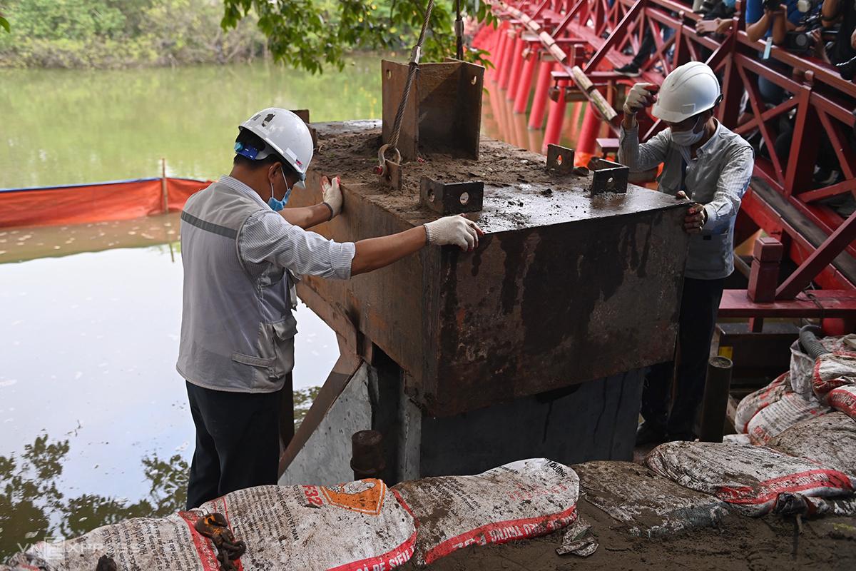 Công nhân dùng máy thủy lực ép khối bê tông xuống đáy hồ. Ảnh: Giang Huy.