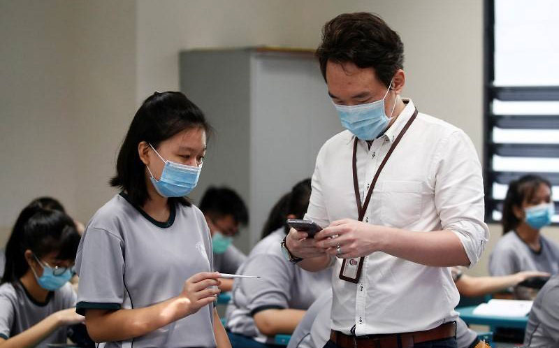 Học sinh trường trung học Yio Chu Kang, Singapore dùng nhiệt kế riêng đo thân nhiệt và báo lại cho giáo viên. Ảnh: Edgar Su/ Reuters.