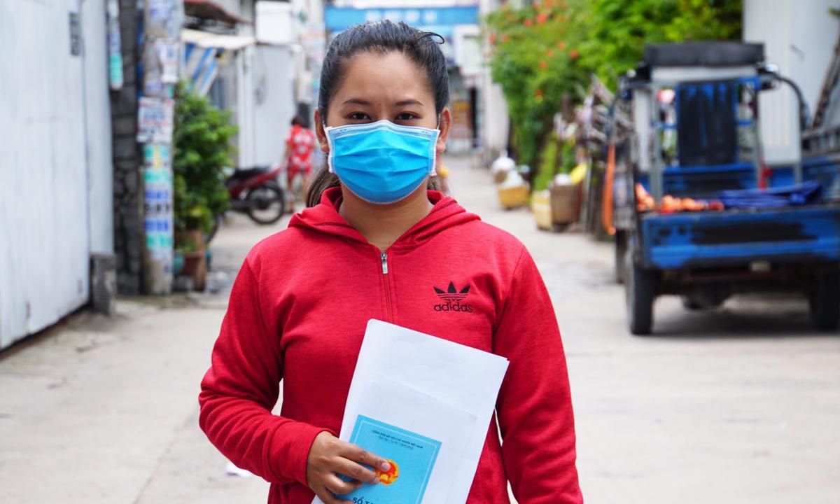 Chị Nguyễn Ngọc Châu, phường Tân Thới Nhất, quận 12 và hồ sơ xin học cho con. Ảnh: Mạnh Tùng.