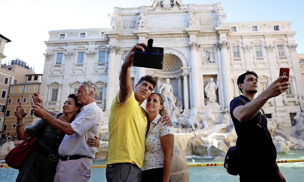 Những người không đeo khẩu trang chụp ảnh trước đài phun nước Trevi ở Rome, Italy, hôm 19/8. Ảnh: Reuters.