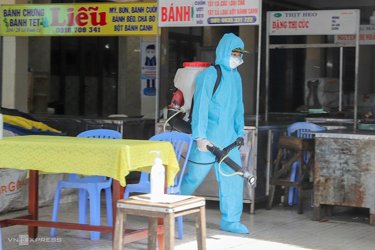 Các chiến sĩ quân đội mang bình phun hoá chất đeo vai tiến sâu vào khử khuẩn khu vực bên trong chợ. Ảnh: Nguyễn Đông.