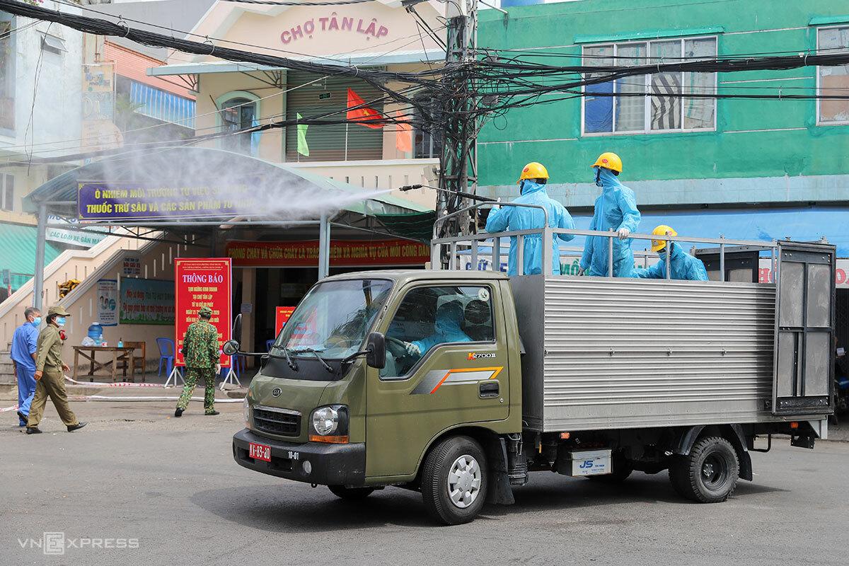 Quân đội phun hoá chất trước cổng chợ Tân Lập. Ảnh: Nguyễn Đông.