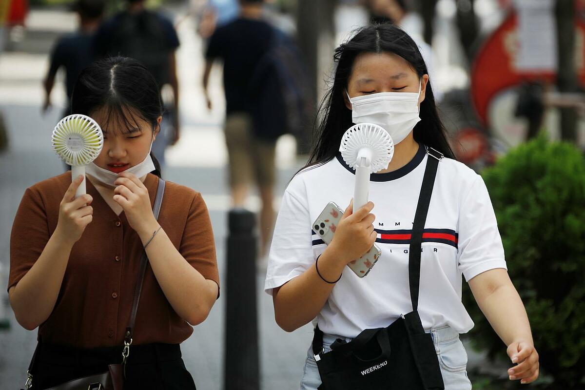 Hai cô gái đeo khẩu trang và dùng quạt di động để làm mát giữa phố Seoul, Hàn Quốc, hôm 20/8. Ảnh: Reuters.