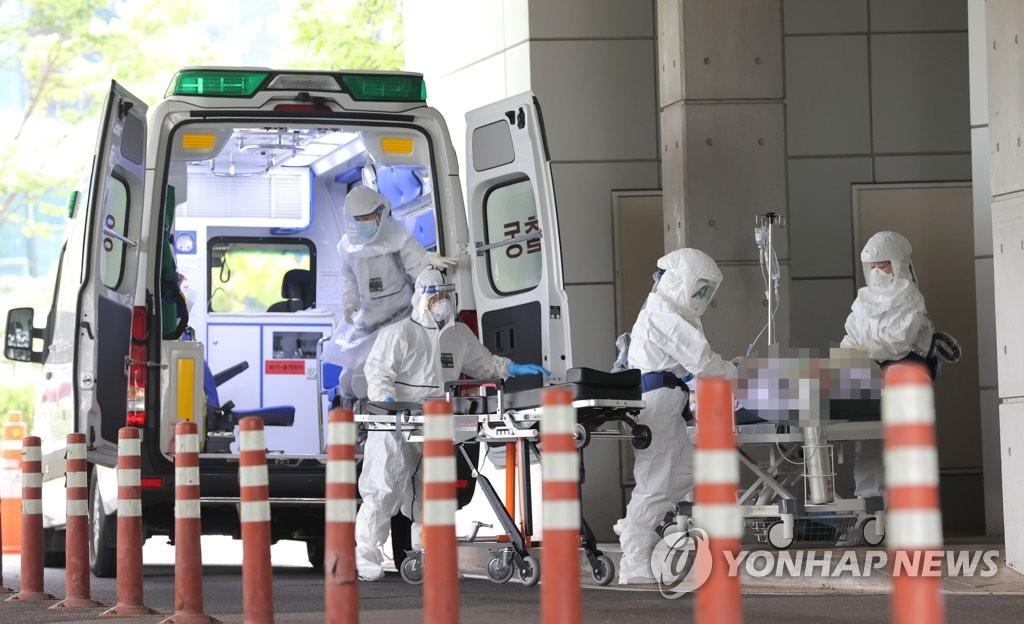 Nhân viên y tế chuyển một bệnh nhân có triệu chứng Covid-19 đến một bệnh viện ở phía bắc Seoul hôm 24/8. Ảnh: Yonhap.
