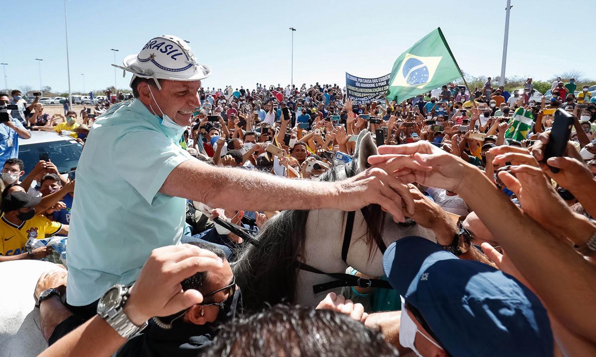 Tổng thống Jair Bolsonaro (trái) cưỡi ngựa bắt tay người ủng hộ tại Sao Raimundo Nonato, bang Piaui  cuối tháng trước. Ảnh: Reuters.