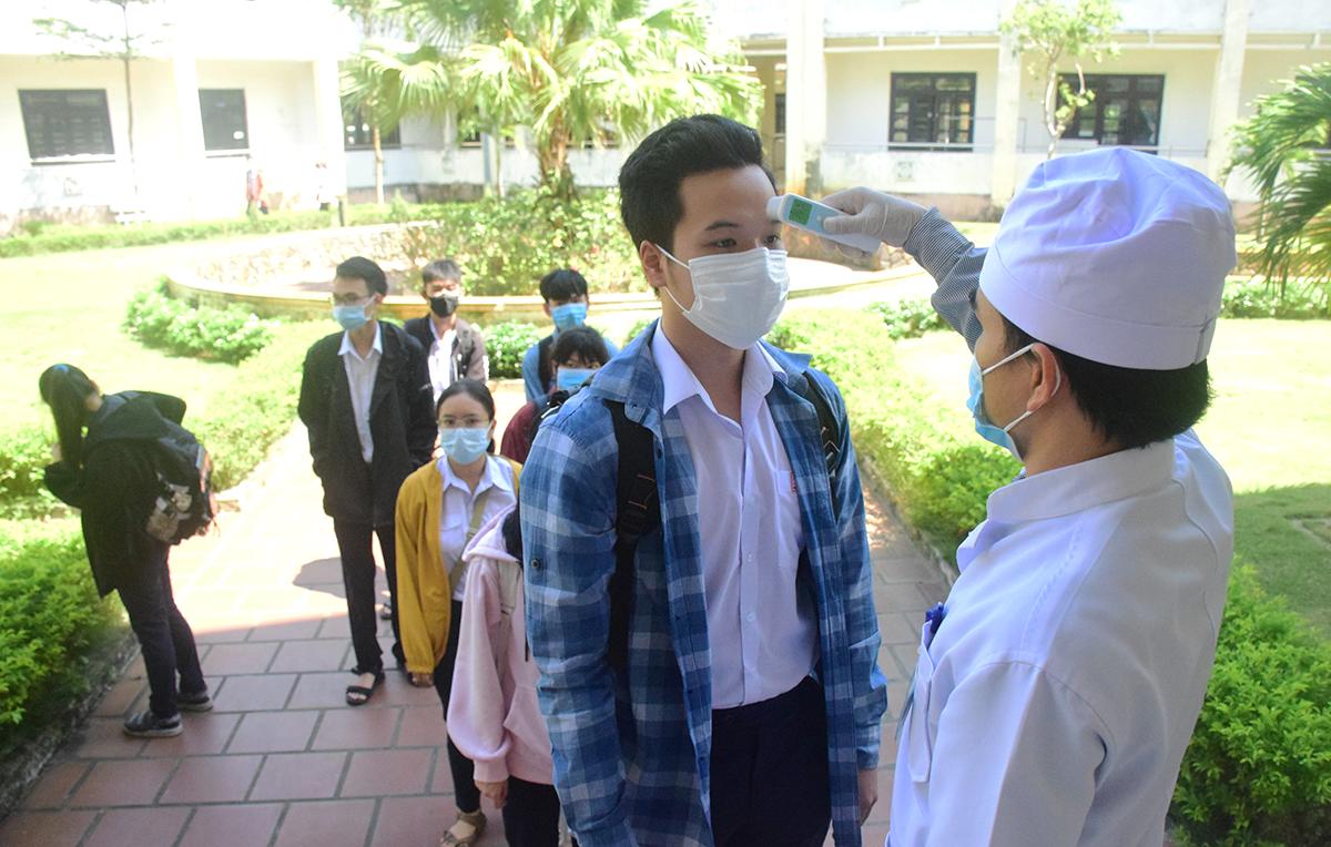 Thí sinh Quảng Nam được đo thân nhiệt trước khi vào phòng thi trong đợt một từ 9-10/8. Ảnh: Đắc Thành.