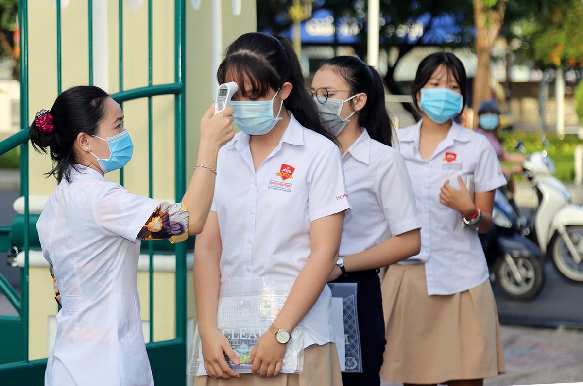 Thí sinh thi tốt nghiệp THPT đợt một ở trường THCS Thái Nguyên, TP Nha Trang đo thân nhiệt trước khi vào phòng thi, sáng 9/8. Ảnh: Xuân Ngọc.