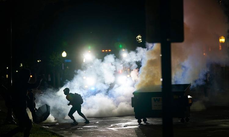 Người biểu tình chạy khỏi làn khói hơi cay tại thành phố Kenosha, bang Wisconsin, Mỹ, hôm 25/8. Ảnh: AP.