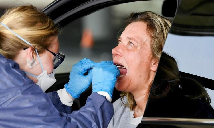 Nhân viên y tế lấy mẫu xét nghiệm nCoV tại một trạm kiểm tra trong xe ôtô ở Alkmaar, Hà Lan, hồi tháng 4. Ảnh: Reuters.