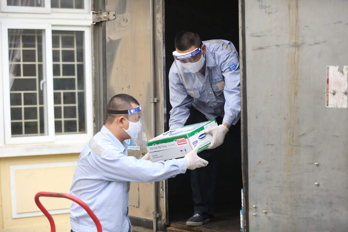 Hai nhân viên Vinamilk vận chuyển sữa đến địa phương tổ chức Sữa học được theo đúng các quy định phòng chống dịch. Ảnh: Nguồn.
