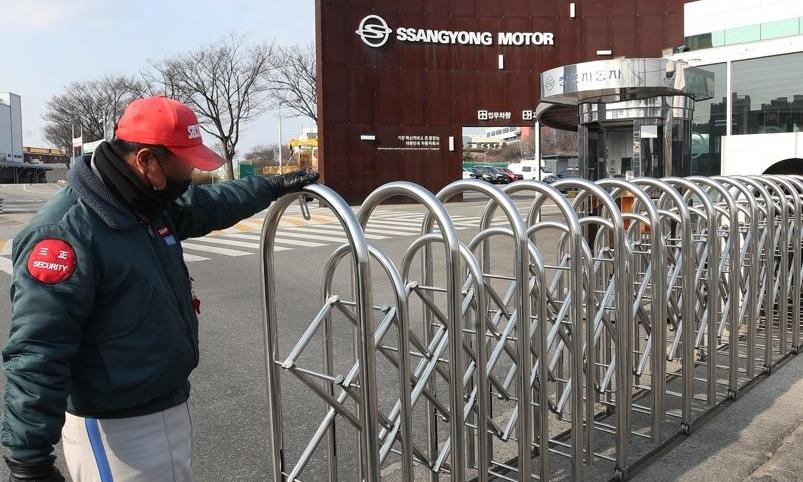 Một bảo vệ đang đóng cổng vào nhà máy SsangYong ở Pyeongtaek, cách thủ đô Seoul 70 km về phía nam, hôm 4/2. Ảnh: Yonhap
