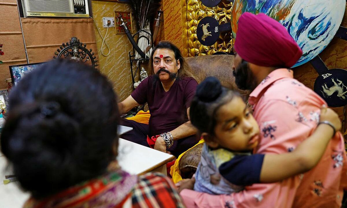 Nhà chiêm tinh Sanjay Sharma (giữa) tư vấn cho khách hàng của ông ở New Delhi, Ấn Độ, ngày 22/8. Ảnh: Reuters.