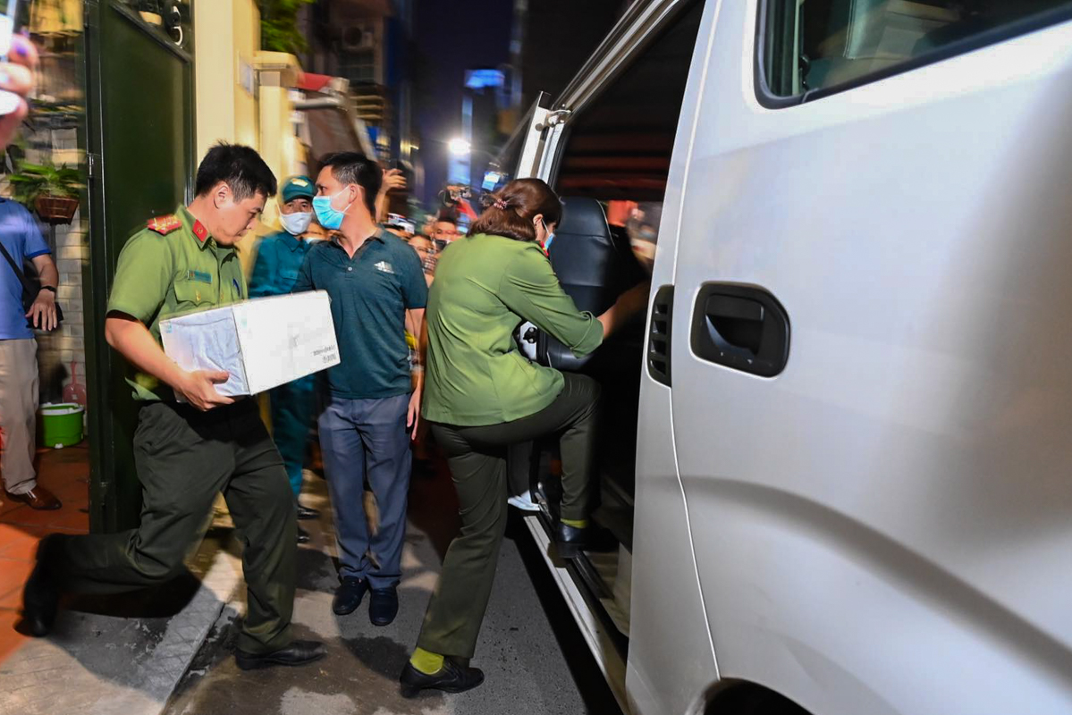 Điều tra viên bê nhiều thùng giấy ra khỏi nhà ông Chung. Hàng trăm người dân vây kín cổng nhà khiến cảnh sát vất vả dẹp trật tự vào tối 28/8. Ảnh: Giang Huy
