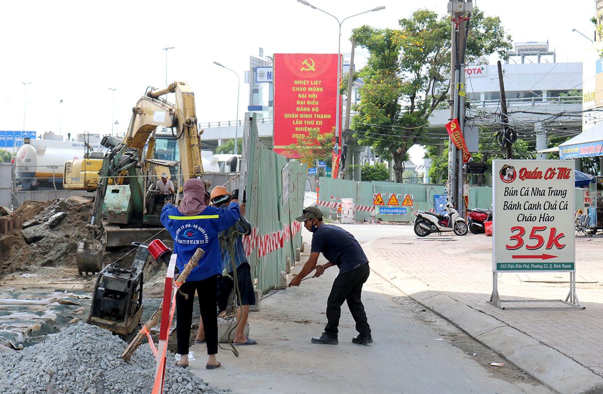 Sau khi chuyển vật liệu vào trong, công nhân dựng lại rào chắn, dài khoảng 30 m trên đường Điện Biên Phủ, đoạn trước quán ăn chị Phụng sáng 30/8. Ảnh: Gia Minh.